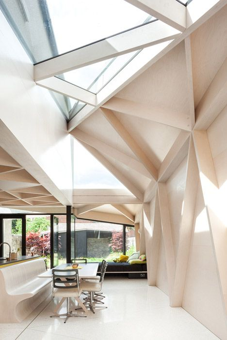 Plywood frames create a pattern of triangles inside house extension by NOJI Architects.