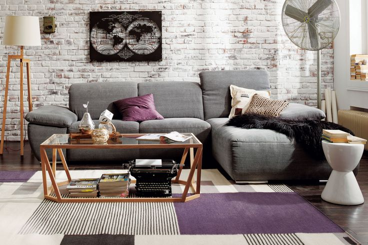Ein graues Ecksofa ist extrem wandelbar. Andersfarbige Kissen lassen das Sofa immer wieder anders aussehen.