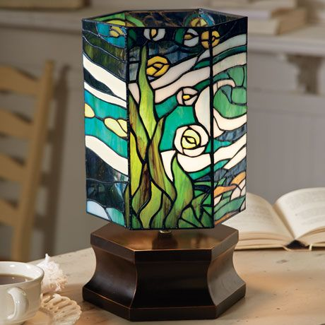 Van Gogh's masterpiece, interpreted in hand-cut glass. In 1889, he painted the view outside his window at Saint-Remy-de-Provence. Today, artists assemble 254 pieces of hand-cut glass in traditional Tiffany style, using the copper foil technique. Hexagonal column rests on a dark brown resin base with bronze accents. Takes a 40-watt bulb (not included). 8 1/2' wide, 15' high.