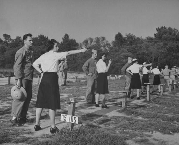Line of Women Accepted for Volunteer Emergency Service, aka the WAVES, practicing pistol marksmenship at a target range under the guidance of military personnel during WWII. US - October 1943
