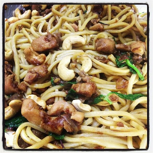 SOY and BASIL CHICKEN NOODLES 1 onion, halved  4 cloves garlic  30g Cobram Estate EVOO  4-6 chicken thighs, diced to 1cm  2 tbsp fish sauce  1 tbsp dark soy  1 tbsp oyster sauce  1 tbsp light tamari or soy  2 tbsp coconut palm sugar  A little water if needed  Generous handful roasted but unsalted cashews  Generous handful Thai basil leaves or regular if you can't get the Thai  1 packet Hokkein noodles  Water for soaking noodles