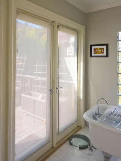 This sheer roman shade woven in delicate grasses and poly, banded in a beautiful raw silk was a great window covering solution to meet our clients need for a high-end look to compliment the marble as well as preserve the view of her garden from her bathroom but lend a little bit of privacy.