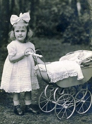 Vintage photo of sweet little girl with doll in a pram, circa 1920 - 1935.