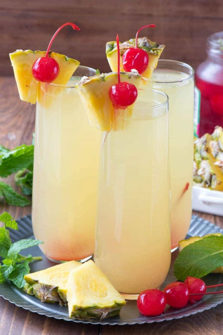 Three Hawaiian Mimosas with cherries and pineapple for garnish.