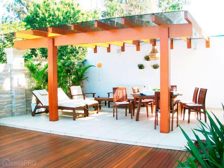 Pergolado feito de madeira com cobertura de vidro laminado fumê e deck do mesmo material. Projeto de Alessanara Maioli.