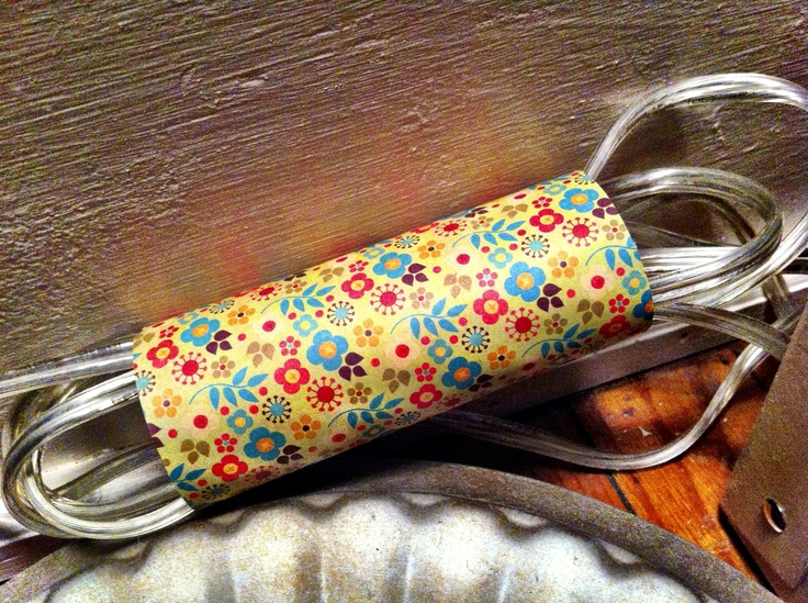 Toilet paper roll turned cord hider/holder. Took a toilet paper roll, glued decorative paper onto it. Easy peazy.