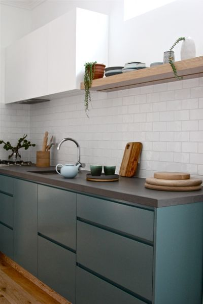 simple semi gloss treatment, concrete counter, wood, creamy tile background. blue with taupe geometric wall paper and green chintz on opposite wall