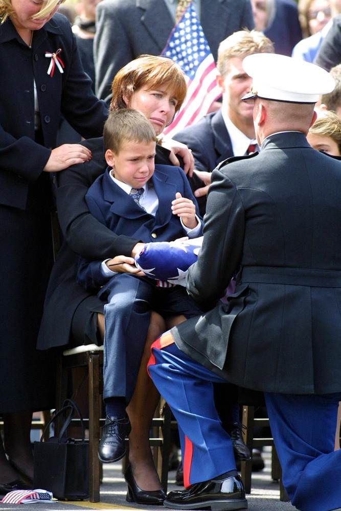 Miriam Horrocks, seated, with 6-year-old son Michael, is presented with the U.S. flag by a U.S. Marine Corps honor guard following a funeral Mass on Sept. 17 in Media, Pa., for her late husband. Michael Horrocks, 38, was killed when hijacked United Airlines Flight 175, which he was co-piloting, crashed into the south tower of the World Trade Center.