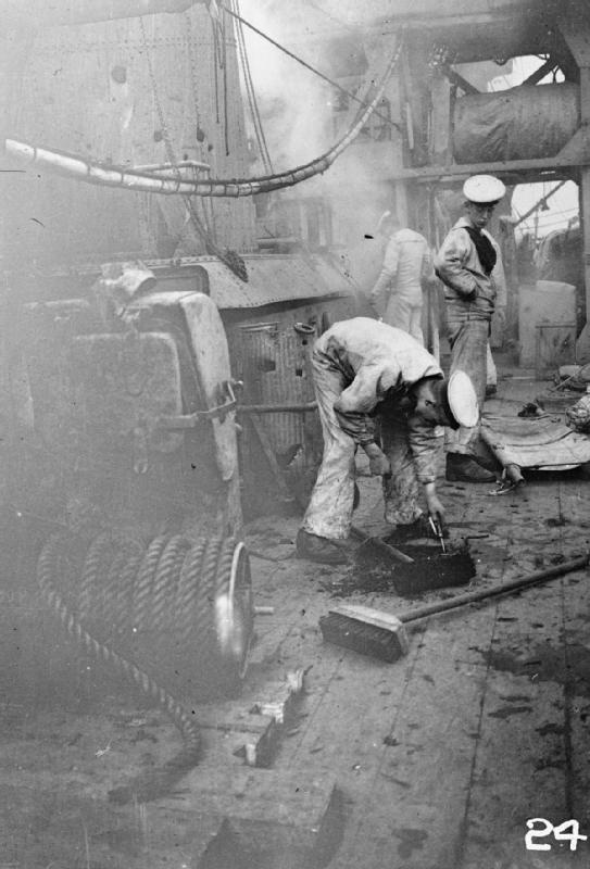 Damage to the deck of HMS CHESTER sustained during the battle of Jutland. Several sailors can be seen on deck including one bending down to inspect the hole. Boy (1st Class) Jack Travers Cornwell was posthumously awarded the Victoria Cross for remaining at the forward gun on board the cruiser. The ship was badly shelled by four German cruisers and Cornwell's position was hit four times, killing all the crew apart from Cornwell. The badly wounded boy sailor was taken back to Grimsby where he…