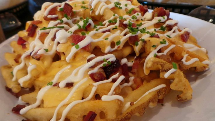 Irish Nachos from Bruxie's Gourmet Waffles found in several Southern California locations.  The nachos are made with crispy waffle fries, Bruxie cheese sauce, crumbled Applewood bacon, sour cream and chives or scallions.  I'm not sure of recipe for Bruxie's cheese so will use melted Cheddar cheese or melted nacho cheese.