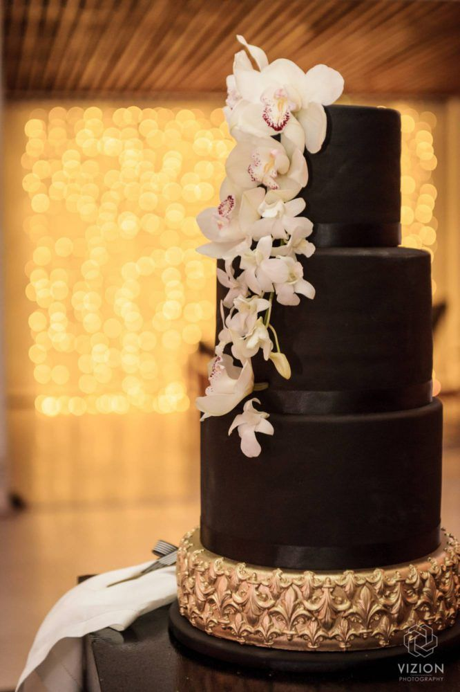 Elize & Stefan Real Wedding Showcase - The Aleit Group  Black and gold wedding. Black and gold wedding cake. Black icing. Black fondant. Lillies on cake. Wedding photos. Gold cake decoration. Vizion Photography and Films. Laurent Venue. South Africa.