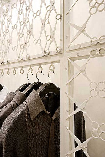 "Fashion designer Rajeesh Pratap Singh's store in the Emporio Mall, New Delhi, India, features scissor walls and hanging space. Architects LOTUS used the tailor's tool as a metaphor of industrial craft to come up with the brilliant design which inserts a ""skin"" - a lacework of scissors - into a generic store space."