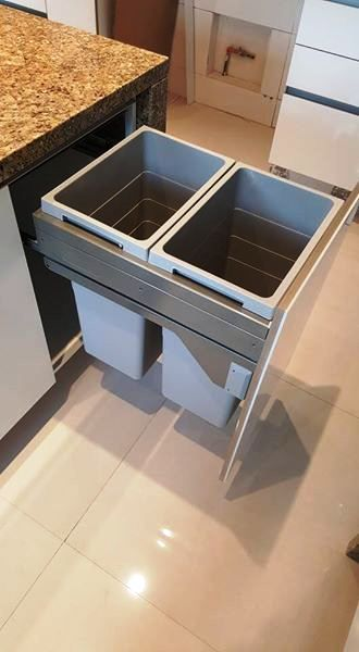 Trash & recycle bins in a drawer next to sink.