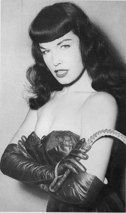 Bettie Page in leather bustier and gloves, holding a whip