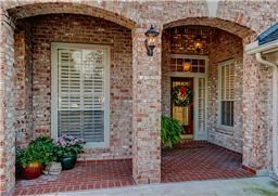 The covered front porch with its decorative brick archways and detailed accents.