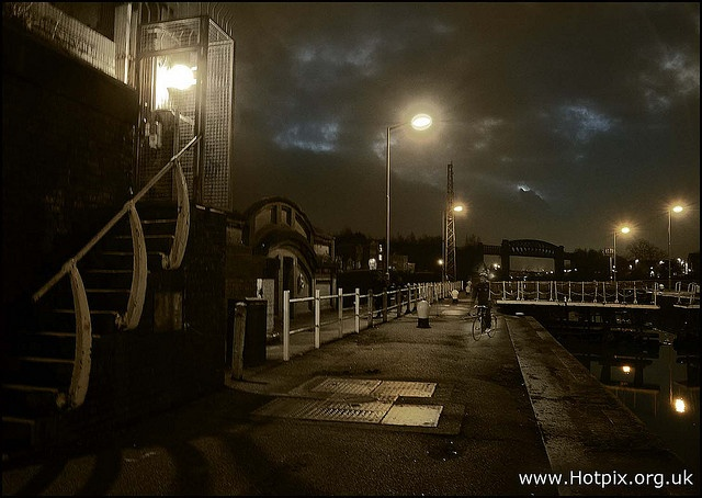 A cyclist crosses Latchford Locks on the Manchester ship canal at dusk. Ships climb approx 20 feet up towards Thelwall and Irlam towards Carrington / Manchester Salford Quays.    Mooring post allows ships to moor temporarily in the dock below or above  http://viettelidc.com.vn