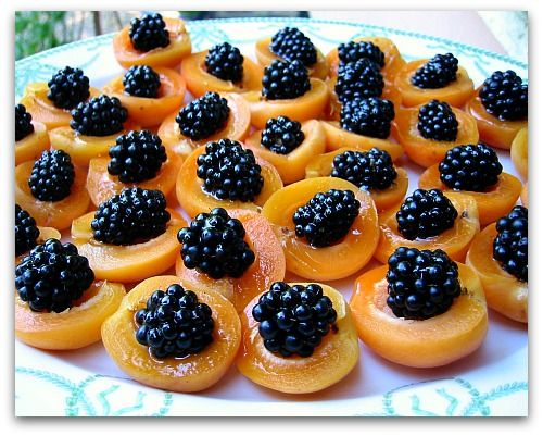Simple and pretty summer appetizer! Just toss berries in honey to coat them and then place in halved, pitted apricot.