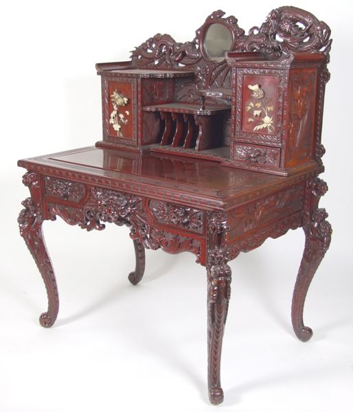 """JAPANESE CARVED AND LACQUERED DESK AND CHAIR (Japanese early 20th c.) Dragon carved crest centered with mirror, tiered shelves, two small doors with applied carved ivory, top with Greek key border, carved and pierced skirt fitted with two short drawers, carved dragon legs. Comes with matching side chair. Condition: chips to ivory, some pieces are in drawer, age appropriate wear otherwise. Dimensions: desk 44""""W., 29""""D., 55""""H., chair 20 1/2""""W., 19""""D., 38""""H."""
