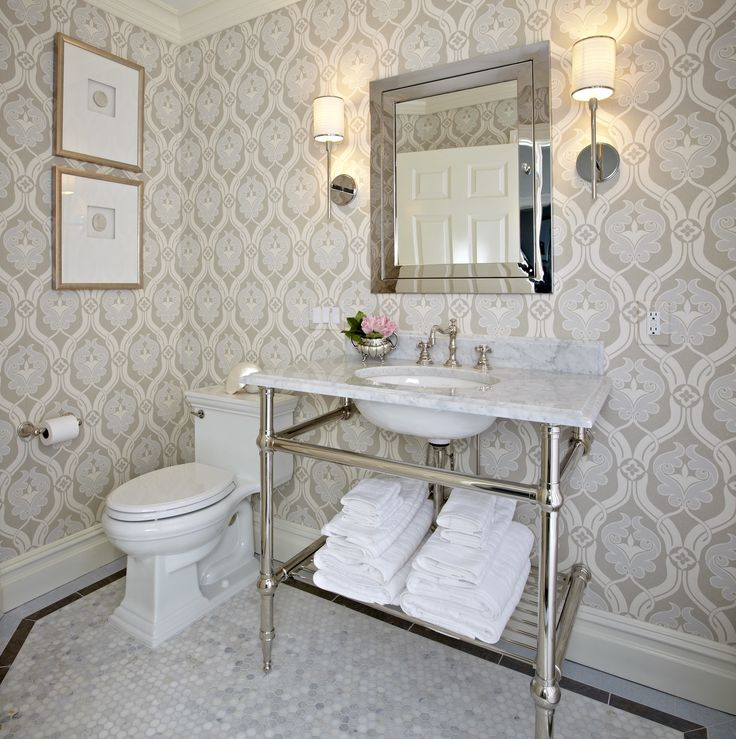 Gallery One Elegant bathroom features a modern purple and gray floral wallpaper lined with a washstand with shelf filled with folded white towels topped with white