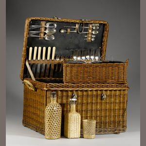A six person picnic basket set by Coracle, 1920s, with lid opening to reveal fitted interior, with lift out tray and accessorie3, the basket 55cm wide.  Sold for £690 inc. premium