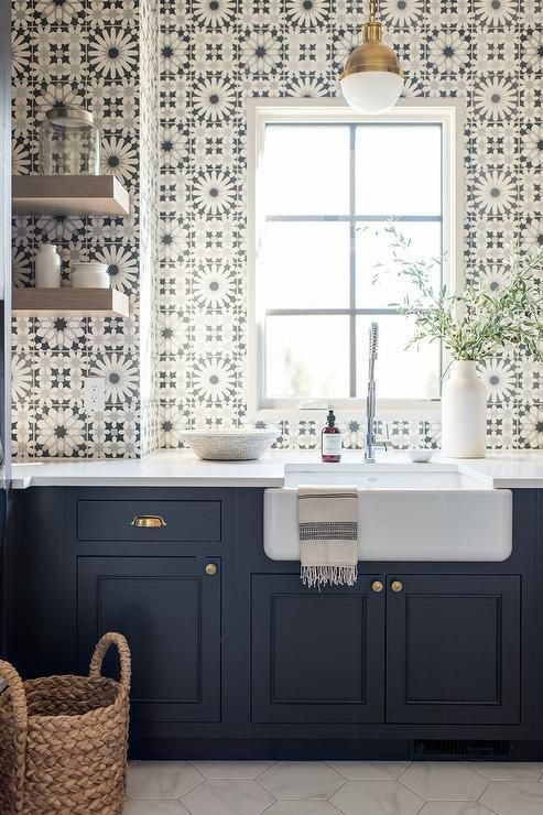Stunning navy blue shaker cabinets accented with brass hardware boast a white counter top fitted with a farmhouse sink paired with a stainless steel pull out faucet lit by a Small Hicks Pendant.
