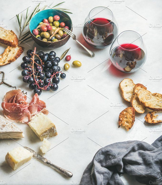 #Wine and snack set  Wine and snack set. Variety of cheese olives in ceramic bowl prosciutto roasted baguette slices black grapes and glasses of red wine over grey marble background selective focus copy space