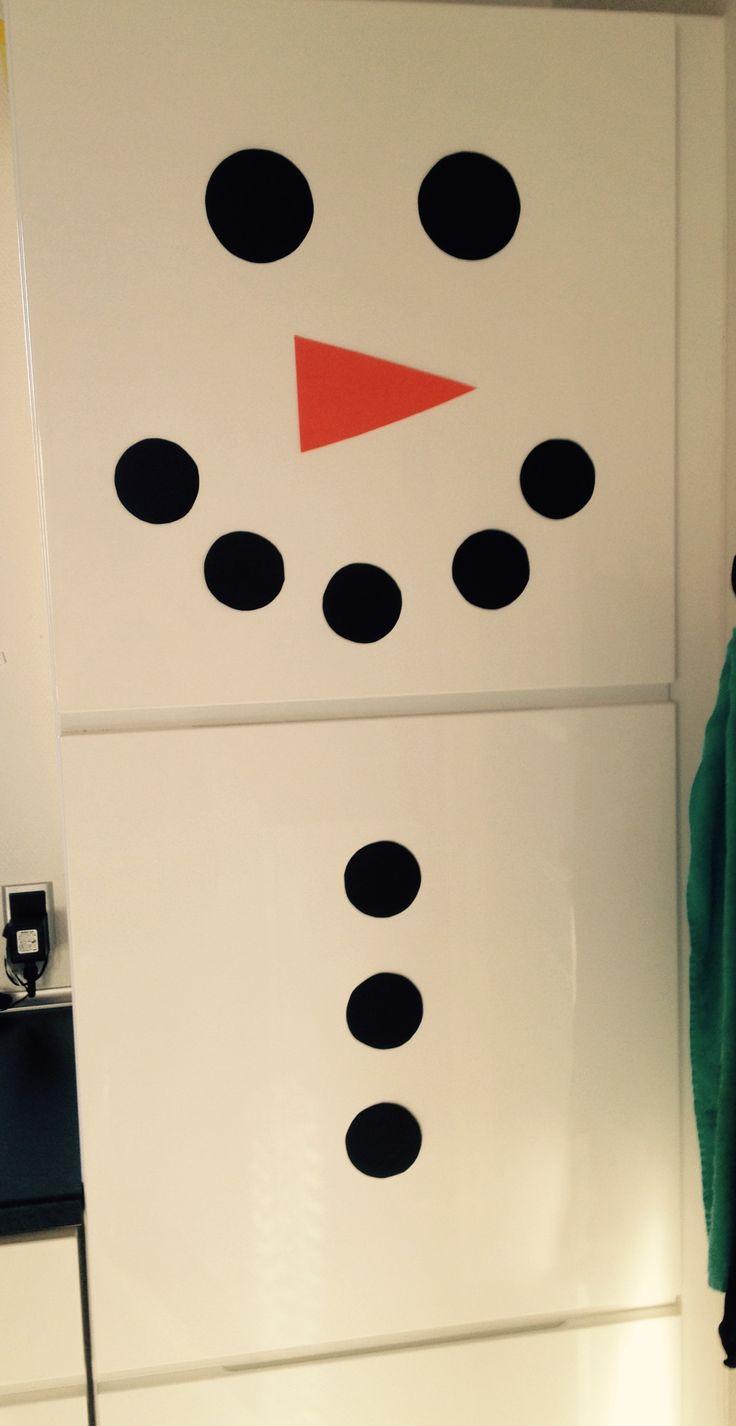 Lav køleskabet, eller en hvid dør, om til en snemand i julemåneden. Brug sort og orange karton.