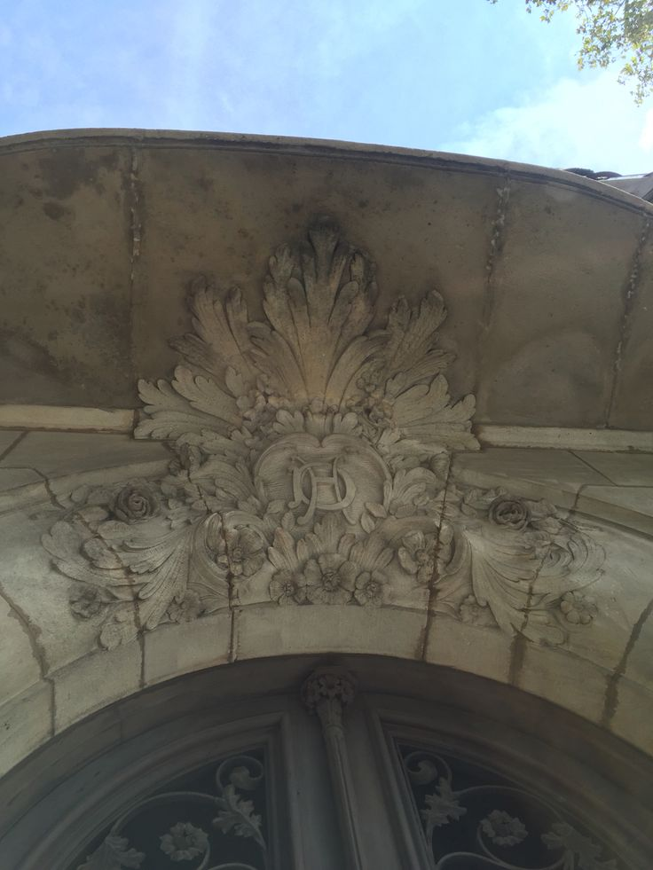 This looks like what the decorations for what would be at the top of a column, with the initials DH? It is an ornate decoration of leaves and flowers at the top of an archway for the door.