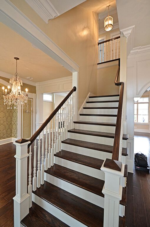 Stained stair treads with wood balusters and newel post.