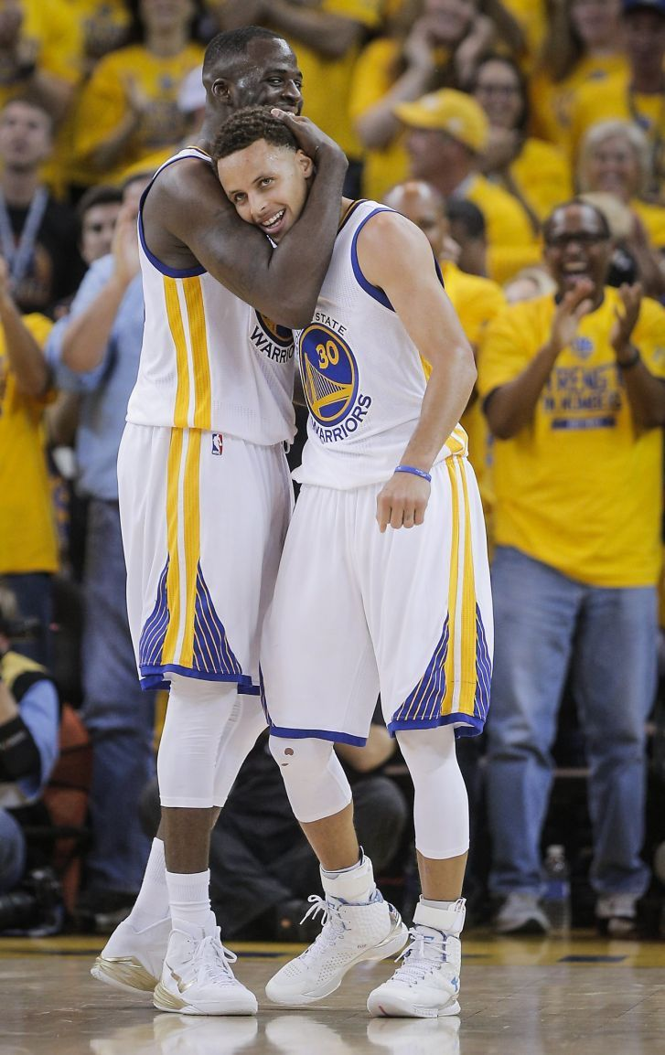 Golden State Warriors' Draymond Green and Stephen Curry embrace in the final minutes of Game 5 of The NBA Finals between the Golden State Warriors and Cleveland Cavaliers at Oracle Arena on Sunday, June 14, 2015 in Oakland, Calif.