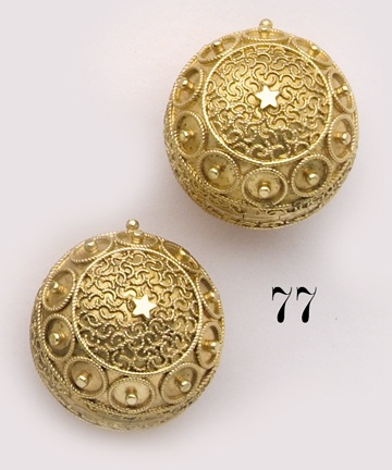 "Pair of hinged Etruscan-revival gold ""coach cover"" earrings. Coach covers were an ingenious device invented in 1878 to disguise and safeguard valuable diamonds while one was traveling in a coach. Sometimes referred to as ""opera covers"", the wearer would ""cover"" the diamonds inside the gold ball, then once inside the opera house, would open the gold balls to reveal diamond earrings inside."