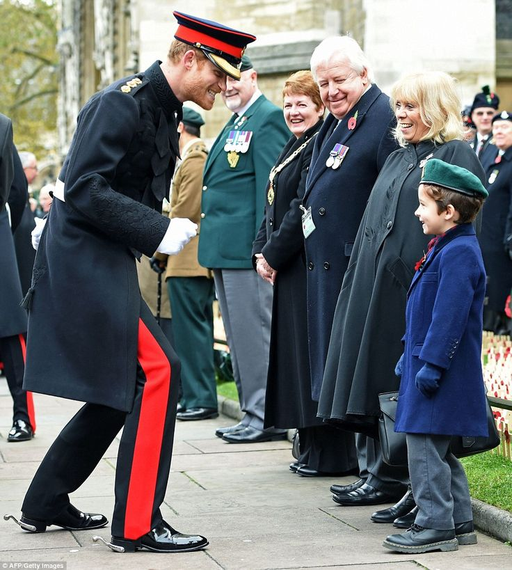 Prince Harry giggles after shaking hands with a young boy during his visit to the Field of...