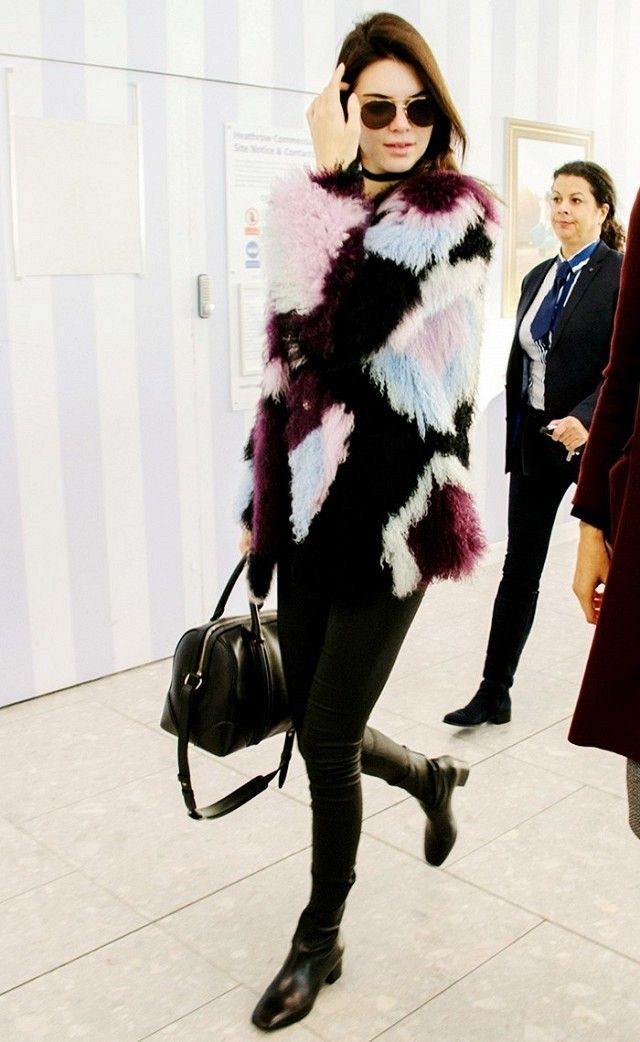 Kendall Jenner wears a patchwork fur coat, leggings, knee-high boots, duffle bag, and aviator sunglasses