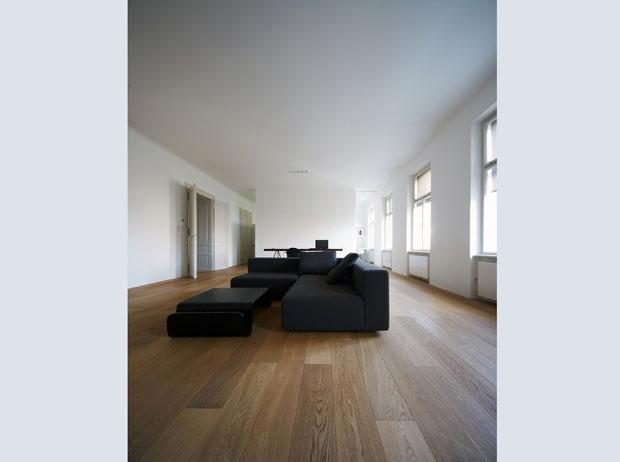 Al centro della zona giorno il living ridotto all'essenziale con una coppia di divani ad angolo e un tavolo basso. Sul fondo la parete aperta ai lati che separa dallo studio e dalla cucina
