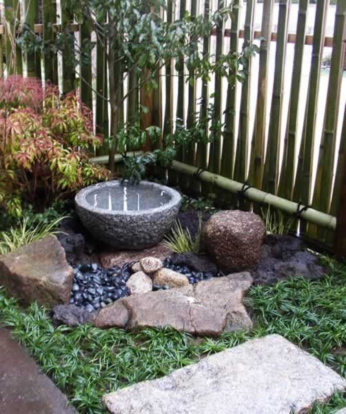 Small space Japanese garden with a tsukubai () at a restaurant in Kyoto,  Japan. A tsukubai is a small basin for ritual ablutions, typically found in  ...