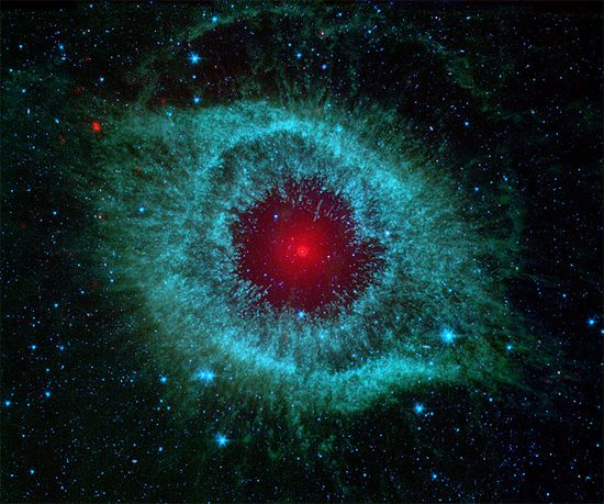 """Nebulosa da Hélice, resultado da morte de uma estrela similar ao Sol. Quando astros desse tipo esgotam seu combustível, eles sopram sua atmosfera para o espaço e tudo que resta é um núcleo compacto, conhecido como anã branca. A nebulosa é o resultado da ejeção do gás estelar. Muitas vezes referida como o """"Olho de Deus"""", ela na verdade é uma janela para o futuro do Sistema Solar. A meros 700 anos-luz de distância, na constelação de Aquário, ela também é um ótimo alvo para astrônomos amadores."""