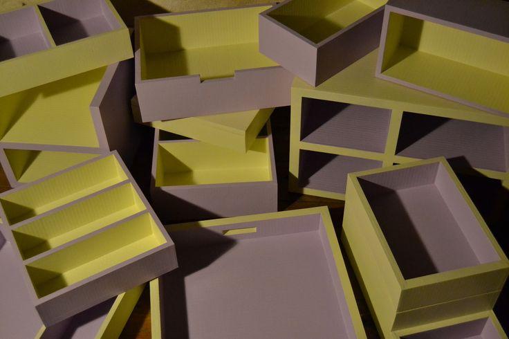 Rangement en carton Un lot de boites et tiroirs de rangement en carton recyclé sur mesure pour l'organisation de diverses choses dans un appartement. Les boites sont en peinture bicolore jaune et mauve. Cuisine - 1 plateau sur machine à laver - 1 boite...