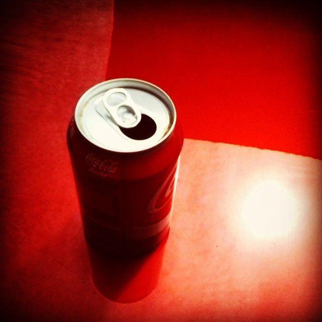 Convergencia en rojo. Un bote de refresco sobre el capó de un coche rojo, la so…