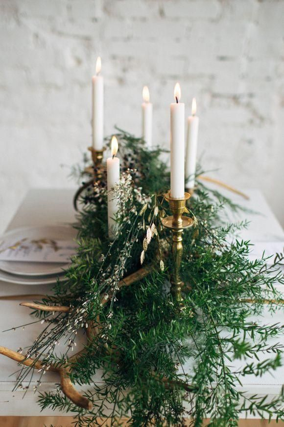 Tablescape with white taper candles, brass candlesticks, and a center garland of ferns. Simple, elegant and romantic.