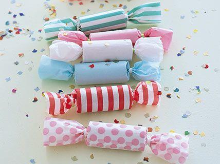 Geschenkpapier mit Streifen und Pünktchen macht die Bonbons schön bunt, im Inneren warten Süßes, Konfetti und Mini-Geschenke. Besonders formvollendet sehen die Bonbons aus, wenn Sie den alten Trick anwenden und eine Papprolle (zum Beispiel vom Toilettenpapier) verwenden.