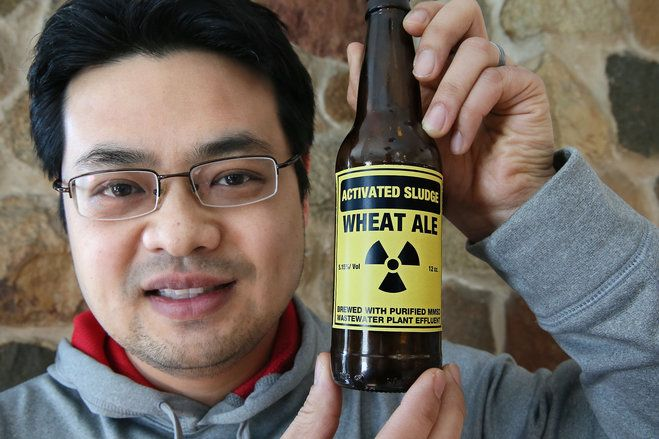 Theera Ratarasarn shows off his home brew, Activated Sludge Wheat Ale beer — brewed using purified Milwaukee Metropolitan Sewerage District wastewater plant effluent.
