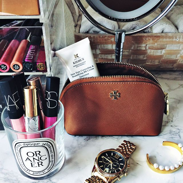 tory burch makeup bag & diptyque candle jar holding lipgloss
