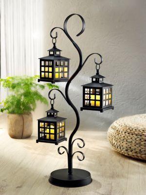 Illuminieren Sie Ihr Wohnambiente stilvoll mit dem Kerzentrio, das in den Laternen des Metall-Bäumchens sanftes Licht spendet. Da die Wachskerzen mit modernen LEDs ausgestattet sind, sind Sie mit dieser Lichtdeko auf der sicheren Seite
