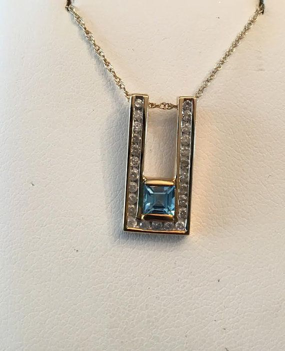 10k yellow gold squared U shaped pendant, with a square Blue Topaz at app. 4.7mm, channel/bar set at the bottom, with 25 round diamonds at app. .13 tw with a color and clarity grading of J-I1,2, channel set around the edges. Marked 10k on the back. Has a double loop bail for the chain to slide through and is suspended from a very fine, loose weave chain at 17.5 marked 10k. The pendant is 3/4 tall by 3/8 wide. Under magnification the blue topaz has some slight facet abrasions se...