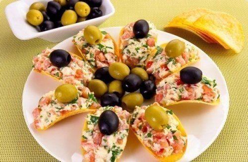 Сырная закуска на чипсах -  Ингредиенты: 100 г сыра 300 г помидоров Зелень по вкусу 2 зубчика чеснока Майонез Картофельные чипсы (широкие) Маслины и оливки (для украшения)