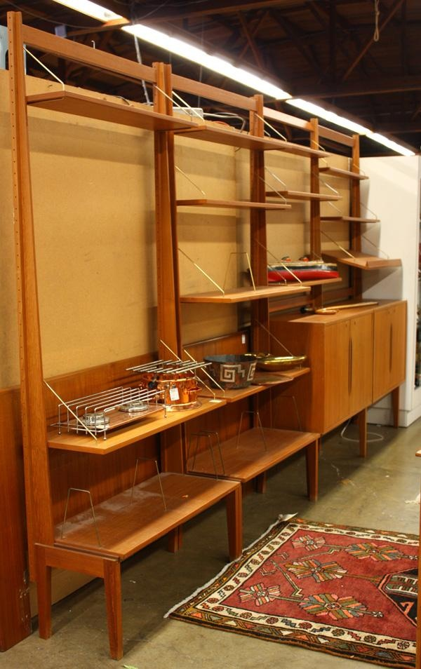 Sold For $1,500 in 2010  Torbjorn Afdal for Bruksbo, Norwegian teak free-standing wall unit, circa 1960, four components, each with adjustable shelves, two with cabinets, seven uprights, label attached inside cabinet, 82.5''h x 144''w x 16''d