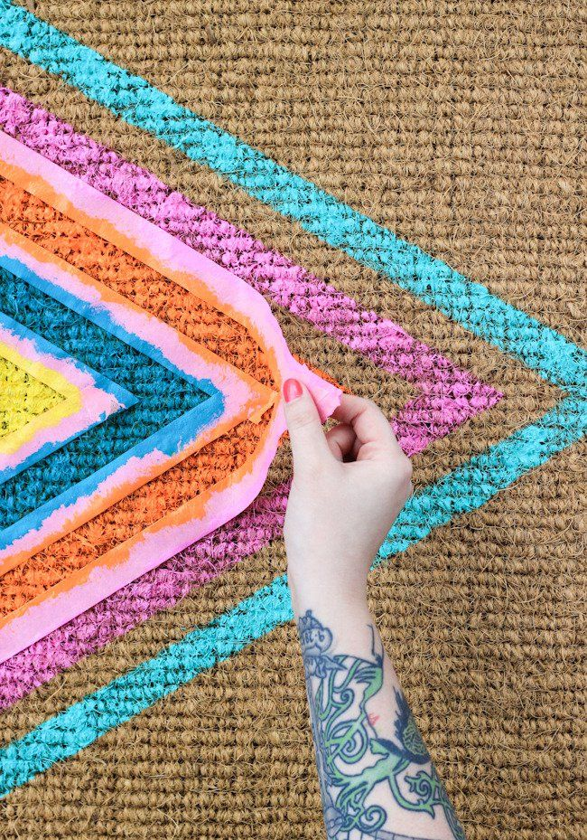 DIY Geometric Welcome Mat: Paint! To really make sure your paint is applied, it helps to almost stamp it into the mat verses painting in brushstrokes.