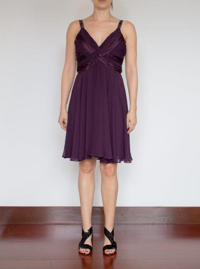 Corto Uva. Vestido corto color uva, Escote en V plisado y cruzado, con caída en carpa y prenses en falda. Adorno de piedras en tiras.