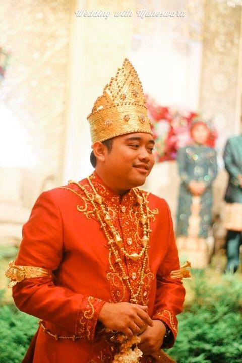 Pengantin pria dalam busana adat pernikahan Lampung Sumatra, mengenakan penutup kepala menyerupai mahkota nan megah.