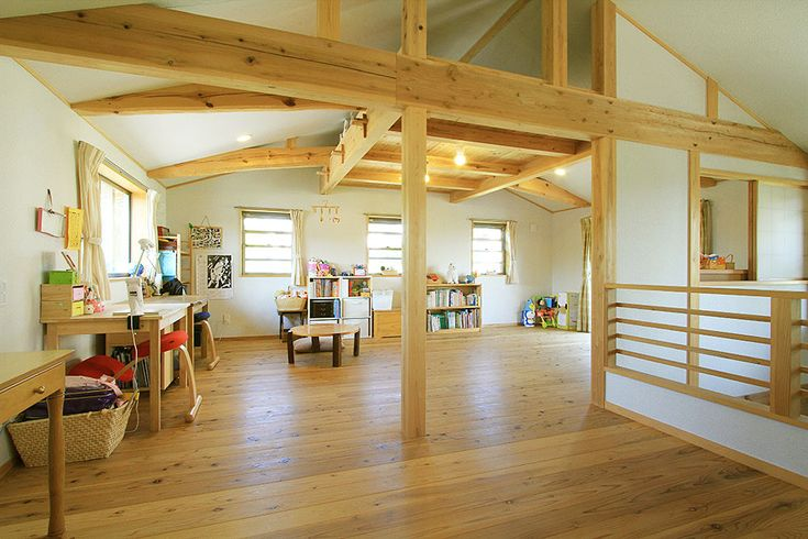 里山が残る郊外に建つ、白い家です。薪ストーブを使っているので、屋根の中央から煙突が伸びています。  立派な土庇がかかった玄関。ガラスのスリットの入った木製建具の扉を開けて中に入ります。  玄関脇の奥には、薪をストックしておくスペースが。薪を集めたり割ったりするのも休日の楽しみです。  薪ストーブのあるリビング。吹き抜けの高いところから明るい光が降り注ぎます。冬はテレビでなく、薪ストーブの炎を見るのも楽しいのです。  リビングの隅にあるキッチンは、火と水と調理台とをL字に配置して使いやすく。カウンターにつくりつけた厚板のテーブルで、朝ご飯ぐらいは済ませることができます。  落ち着いた雰囲気の和室。家にひとつは和室があると、何かと便利です。  洗面所とトイレ。トイレの扉は板を横張りにして、木目をきれいに配置しました。  2階は子どもたちがフリースペースとしてのびのびと使っています。  曲がった梁やまっすぐな梁をあたりまえのものとして見ながら、子ども達が時間を過ごします。木に見守られながら、成長するのです。…